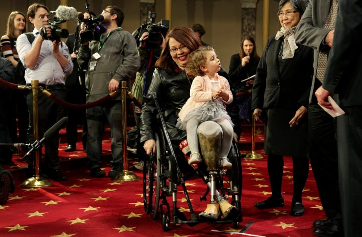 Senator Tammy Duckworth (D-IL) carries her daughter Abigail during a mock swearing in with U.S. Vice President Joe Biden during the opening day of the 115th Congress on Capitol Hill in Washington