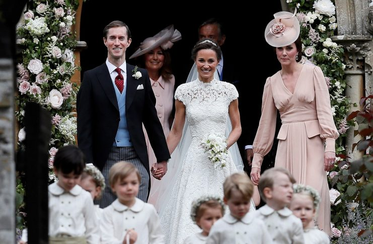Pippa Middleton and James Matthews smile as they are joined by Britain's Catherine, Duchess of Cambridge after their wedding at St Mark's Church in Englefield